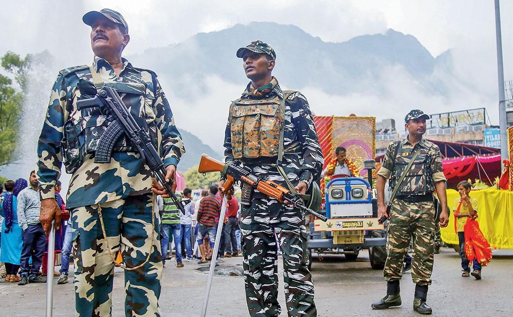 CRPF soldiers stand guard during a procession at Katra near Jammu on Sunday.