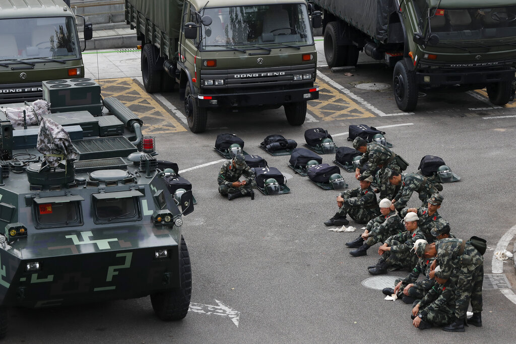Paramilitary policemen practice bandaging each other near armored vehicles and trucks parked outside the Shenzhen Bay Sports Center in Shenzhen, China's Guangdong province, Wednesday, Oct. 30, 2019.