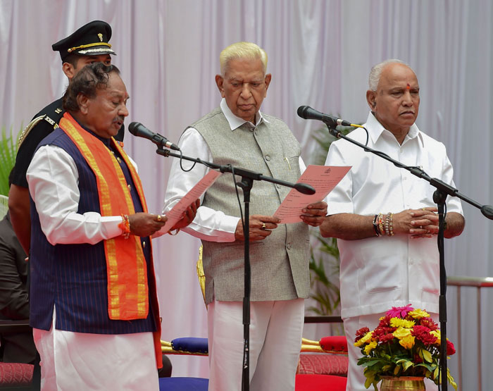 Karnataka Governor Vajubhai Vala (centre) administers the oath of office and secrecy to K S Eshwarappa (left) during the swearing-in ceremony of Karnataka BJP Government, at Raj Bhavan in Bengaluru, on Tuesday, August 20, 2019. Chief minister BS Yeddyurappa is on the right