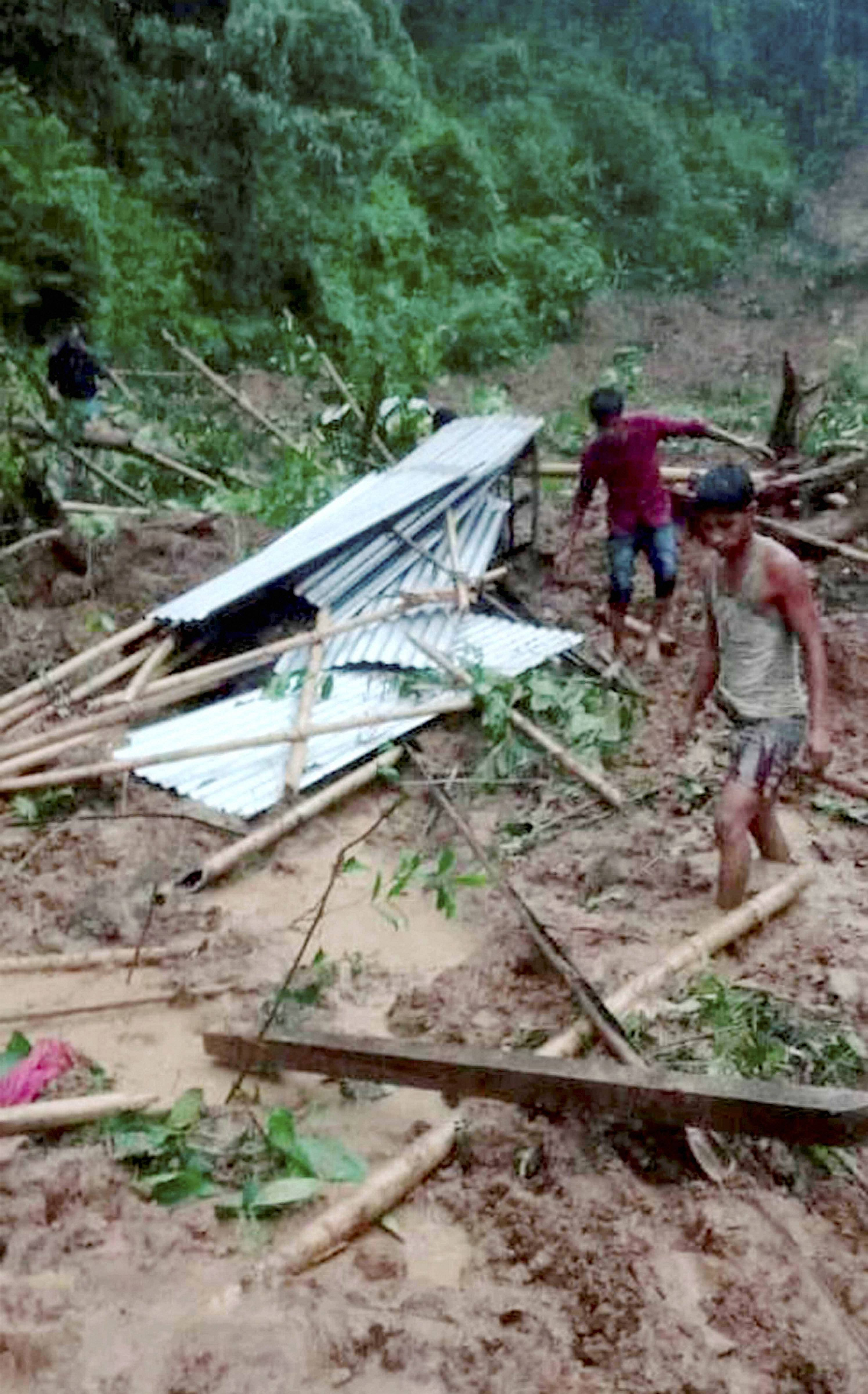 Local residents gather at the spot where the landslide occurred leading to the death of at least six people, in Karimganj district, Tuesday, June 2, 2020