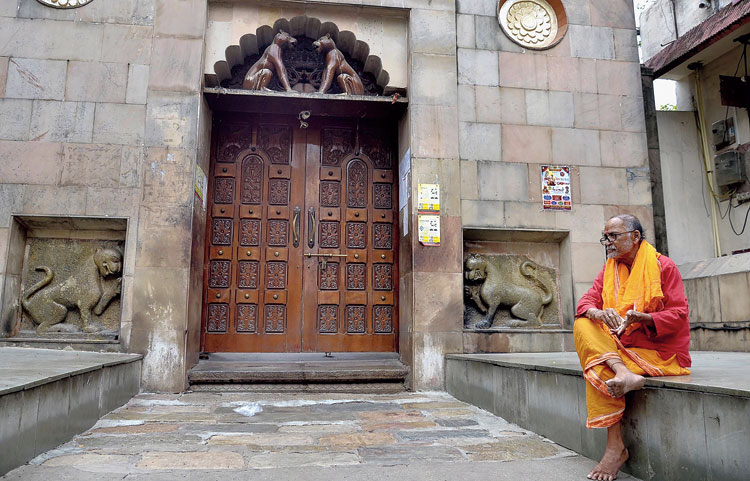 A priest sits outside the closed door of Kamakhya temple in Guwahati on Friday.