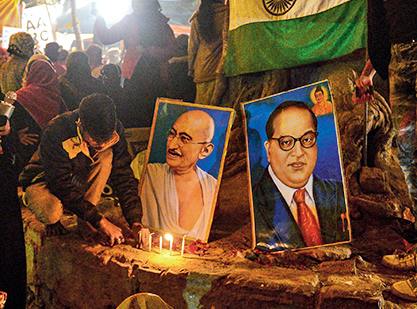Protesters light candles near posters of Mahatma Gandhi (C-L) and politician and social reformer Bhimrao Ramji Ambedkar (C-R) during a demonstration against India's new citizenship law at Mansoor Ali Park in Allahabad on January 14, 2020