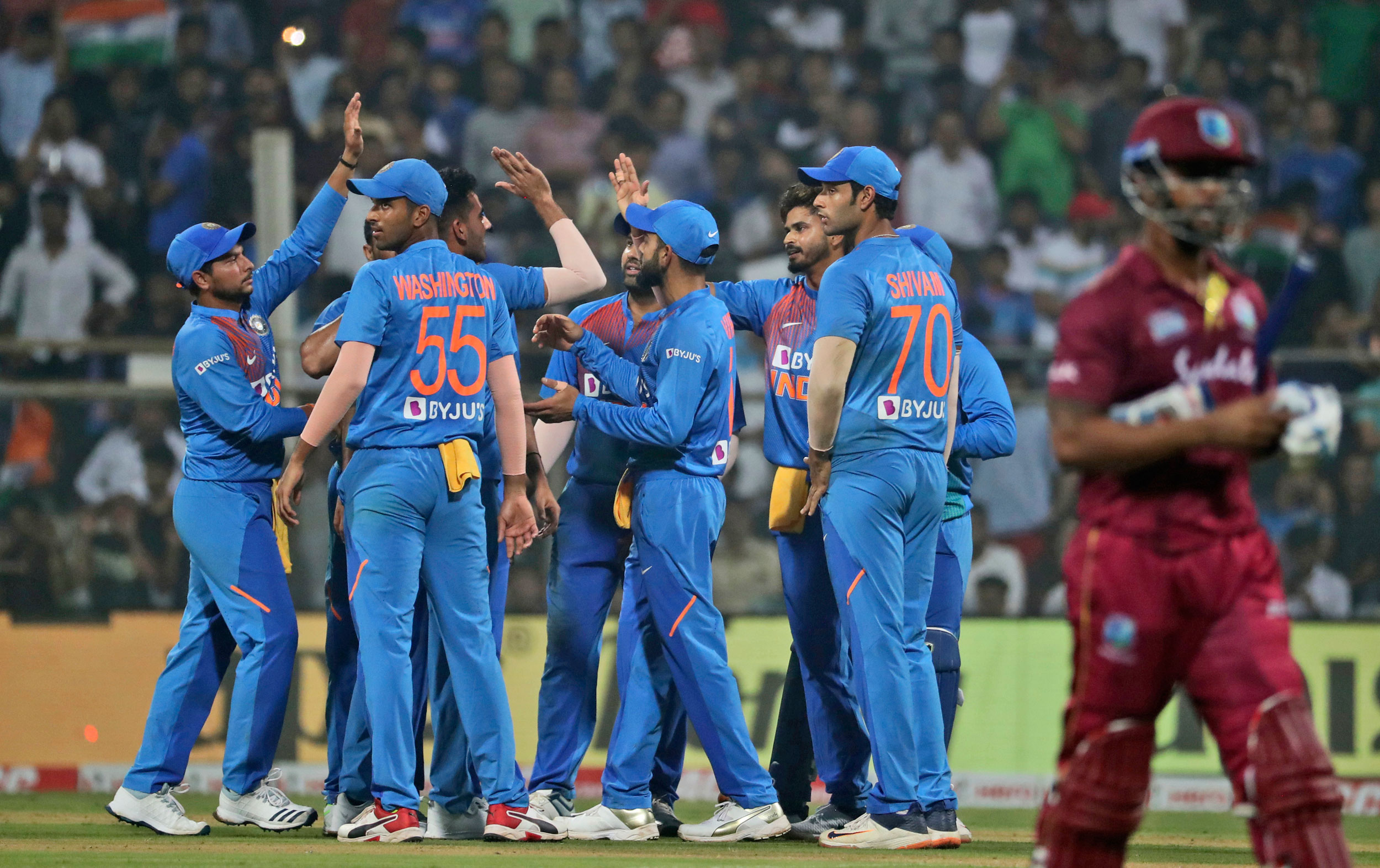 Indian cricketers celebrate the dismissal of Lendl Simmons during the third Twenty20 international cricket match between India and West Indies in Mumbai on Wednesday.