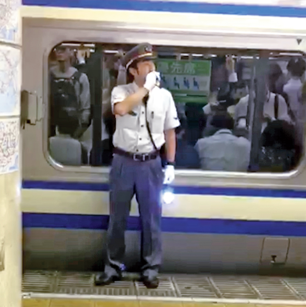 An official talks on the walkie-talkie to supervise passengers boarding and deboarding trains at a Metro station in Tokyo's suburb