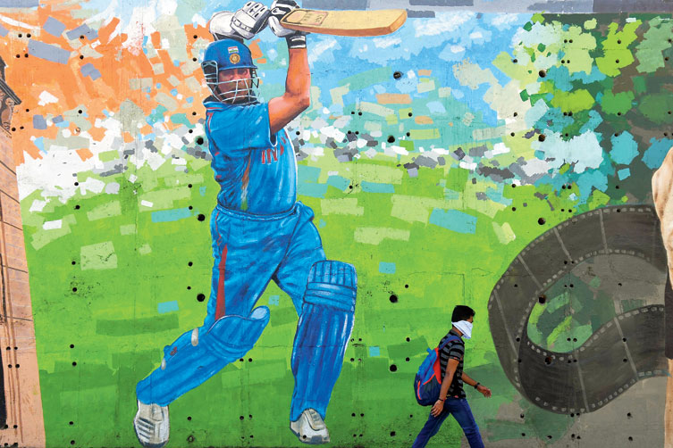 A man passes by a mural of Sachin Tendulkar in Mumbai on Thursday.