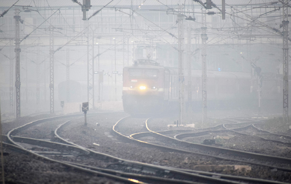 A train slows down as fog envelopes railway tracks on a cold morning in Allahabad on December 12