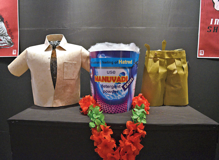 """Exhibits designed by Somsankar Ray in the lobby of Uttam Mancha, the venue of Kolkata People's Film Festival. The cardboard cut-out in the centre resembles the front of a detergent powder pack. The slogan on it — """"For a strong feeling of hatred, use Manuvadi Excel detergent powder"""". A shirt whose buttons are open and a pair of khaki shorts are on two sides of the cut-out. """"The shirt is not fitting because the chest is too broad,"""" said Kasturi Basu, a member of a collective that organsised the festival."""