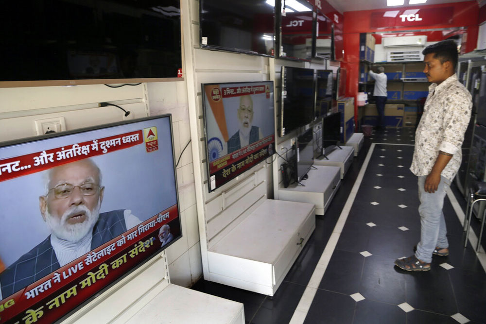 A salesman watches Prime Minister Narendra Modi addressing the nation on a television in Mumbai on Wednesday.