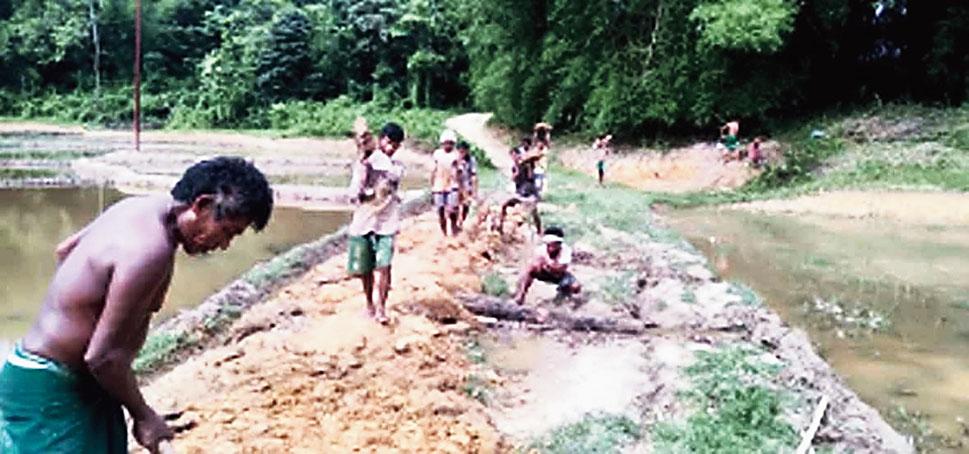Villagers repair the road.