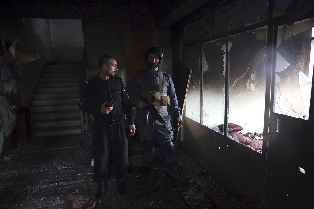 Afghan security personnel inspect a Sikh house of worship, in the aftermath of a deadly attack in Kabul, Afghanistan, Wednesday, March 25, 2020.