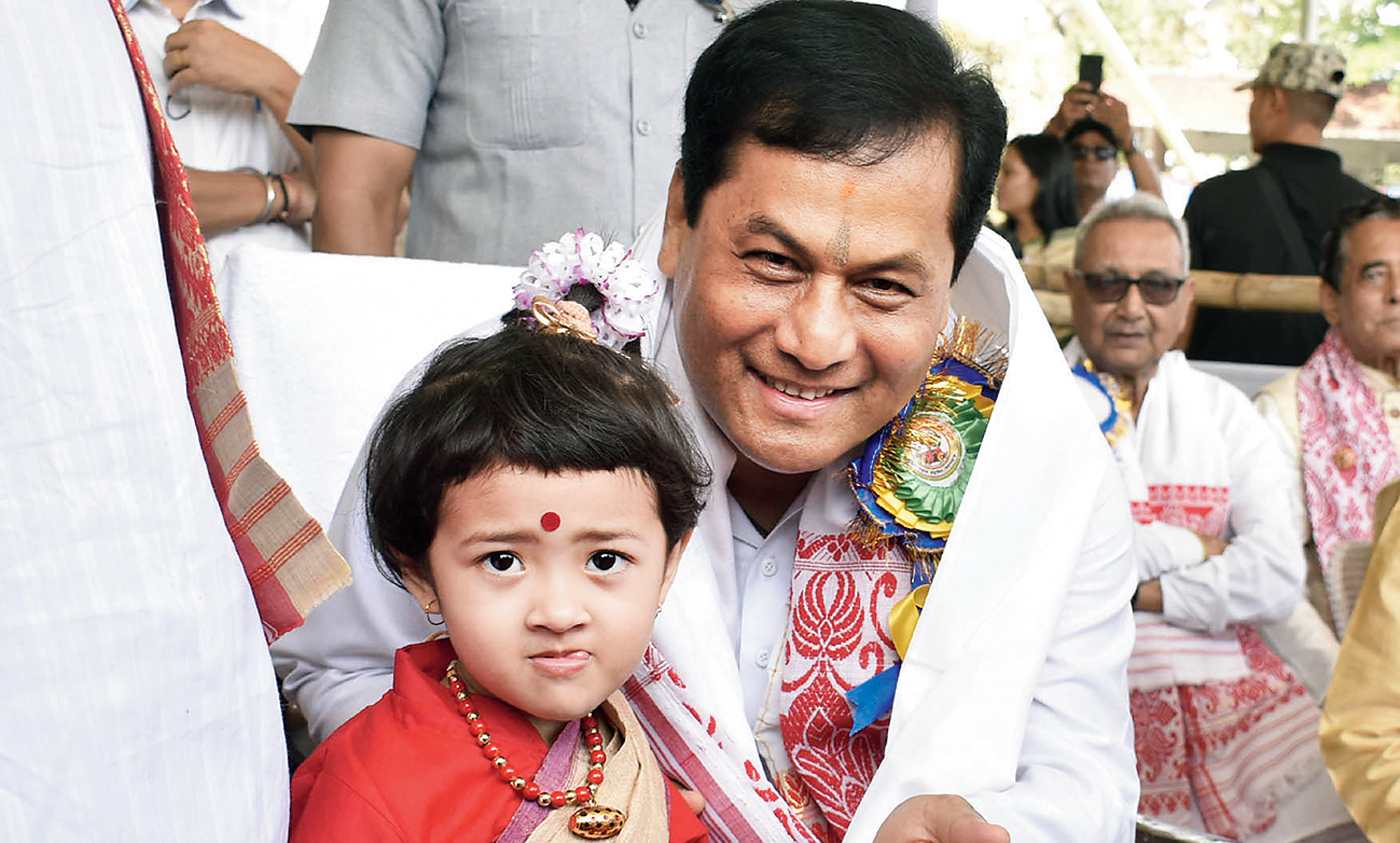 Assam chief minister Sarbananda Sonowal speaks to a girl during the Rongali Bihu celebrations at Latasil playground in Guwahati on Sunday.