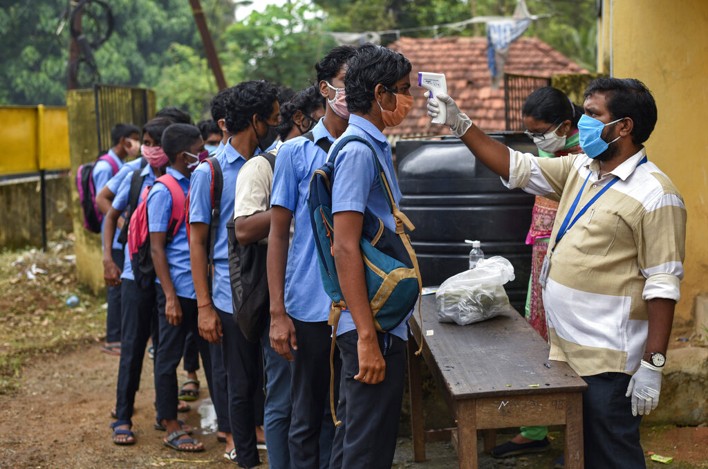 School children wearing masks line up to get their hands sanitized and temperatures checked as they arrive to appear for state board examination during the coronavirus pandemic in Kochi, Tuesday, May 26, 2020.