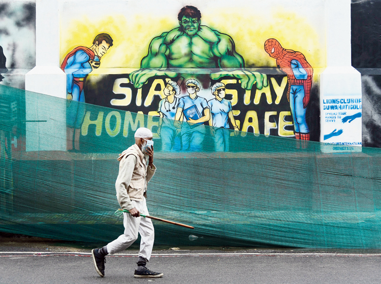 Mask super power: A man walks past a mural with superheroes asking to take precautions against coronavirus in Guwahati on Friday.