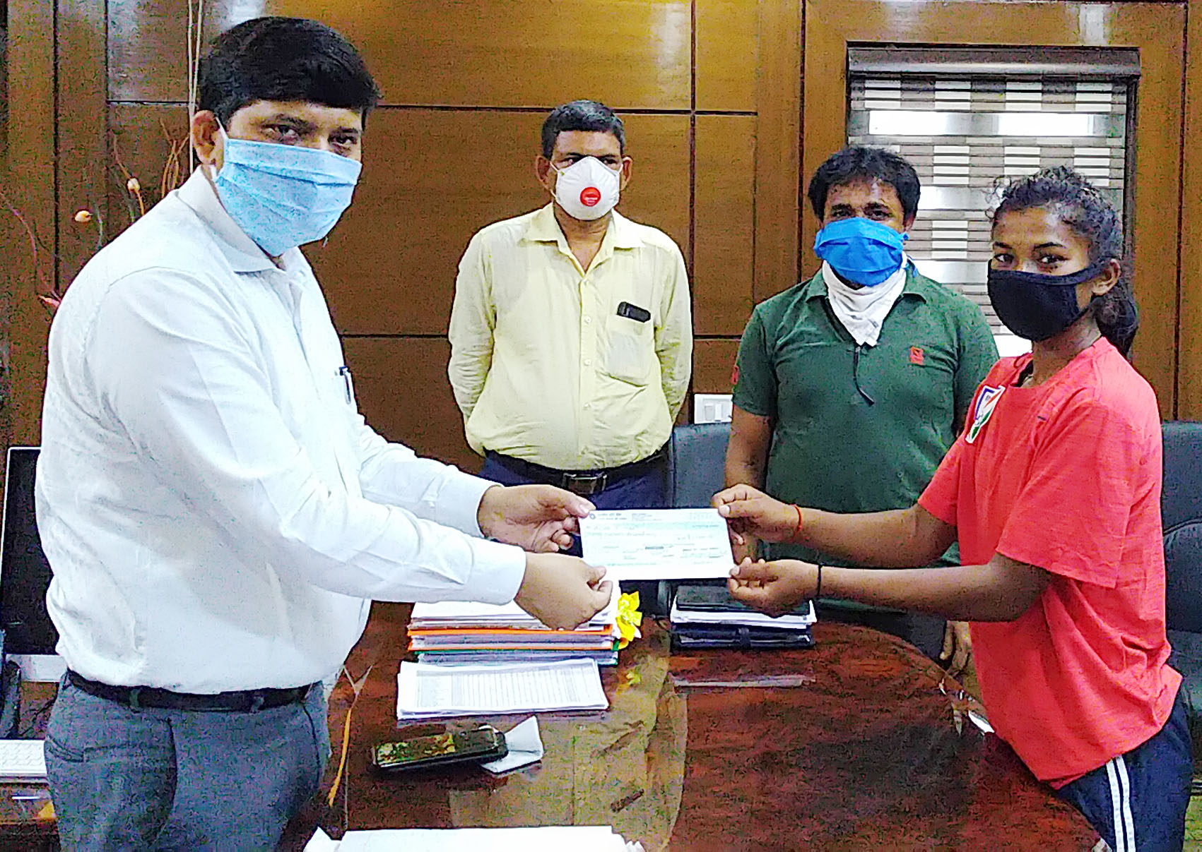 Dhanbad deputy commissioner Amit Kumar hands over a cheque for Rs 15,000 to Asha Kumari at his office on Sunday