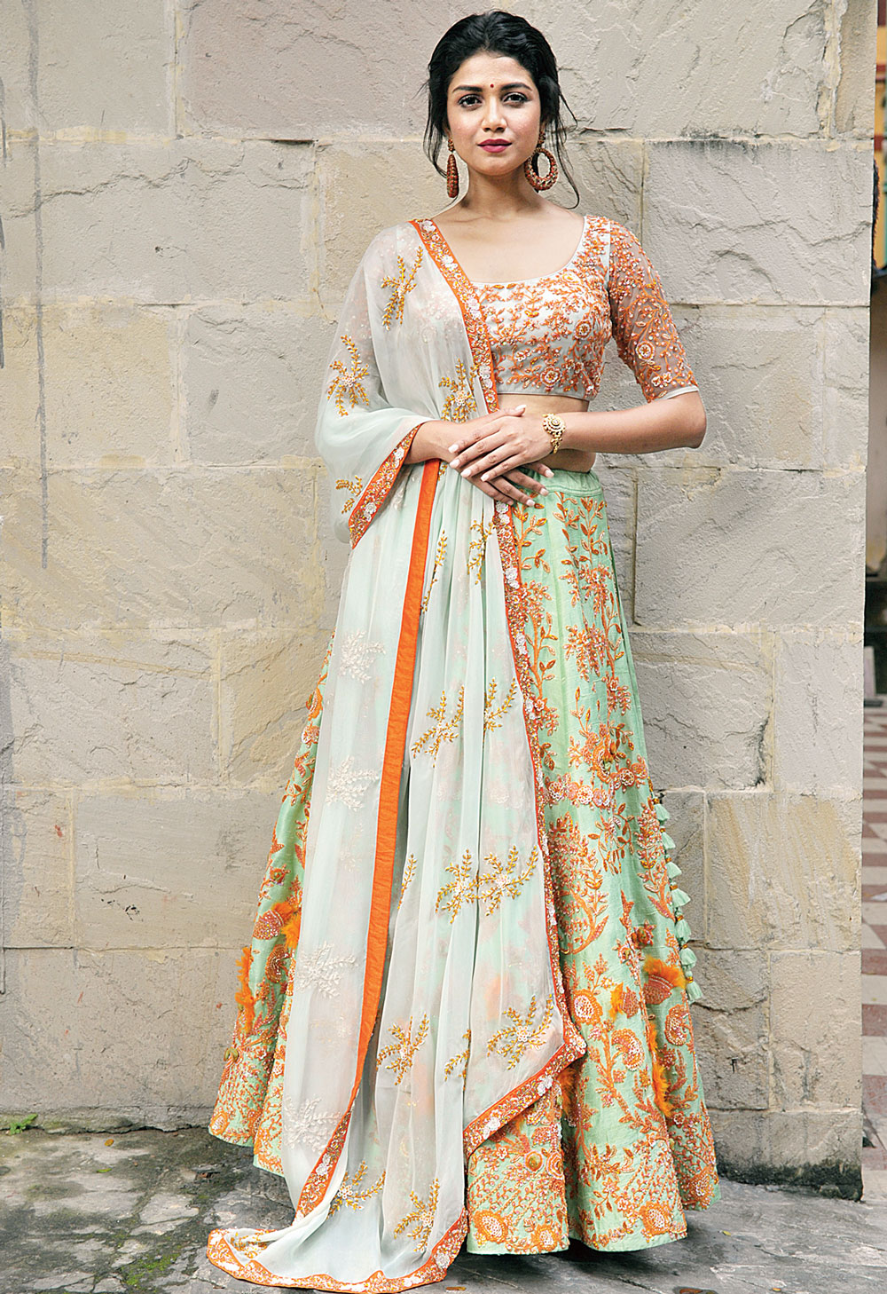 Go traditional yet trendy in an easy-breezy lehnga for the mehndi. With hand-embroidery and orange sequin detailing, this is made with a mix of net and silk, and paired with a light net dupatta