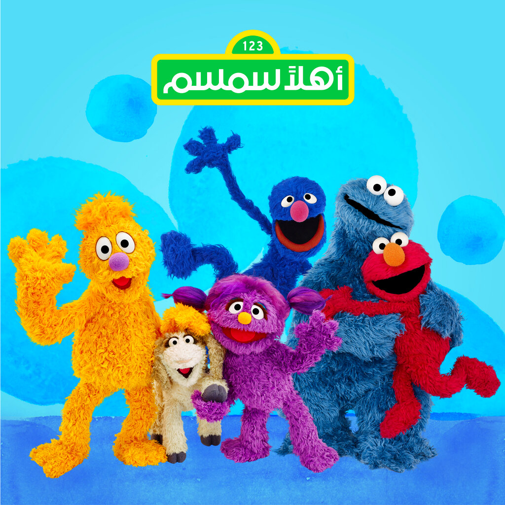 This image released by Sesame Workshop shows characters, from left, Jad, Ma'zooza, Basma, Grover, background center, Cookie Monster and Elmo.