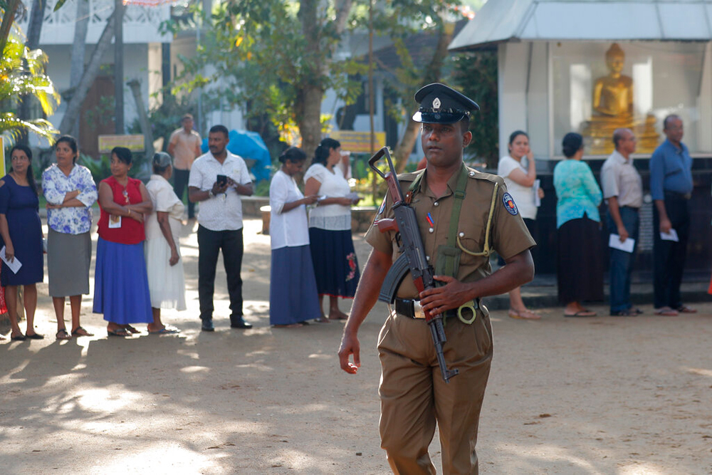 People queue to cast their votes as a police officer stands guard at a polling station in Colombo, Sri Lanka, on Saturday