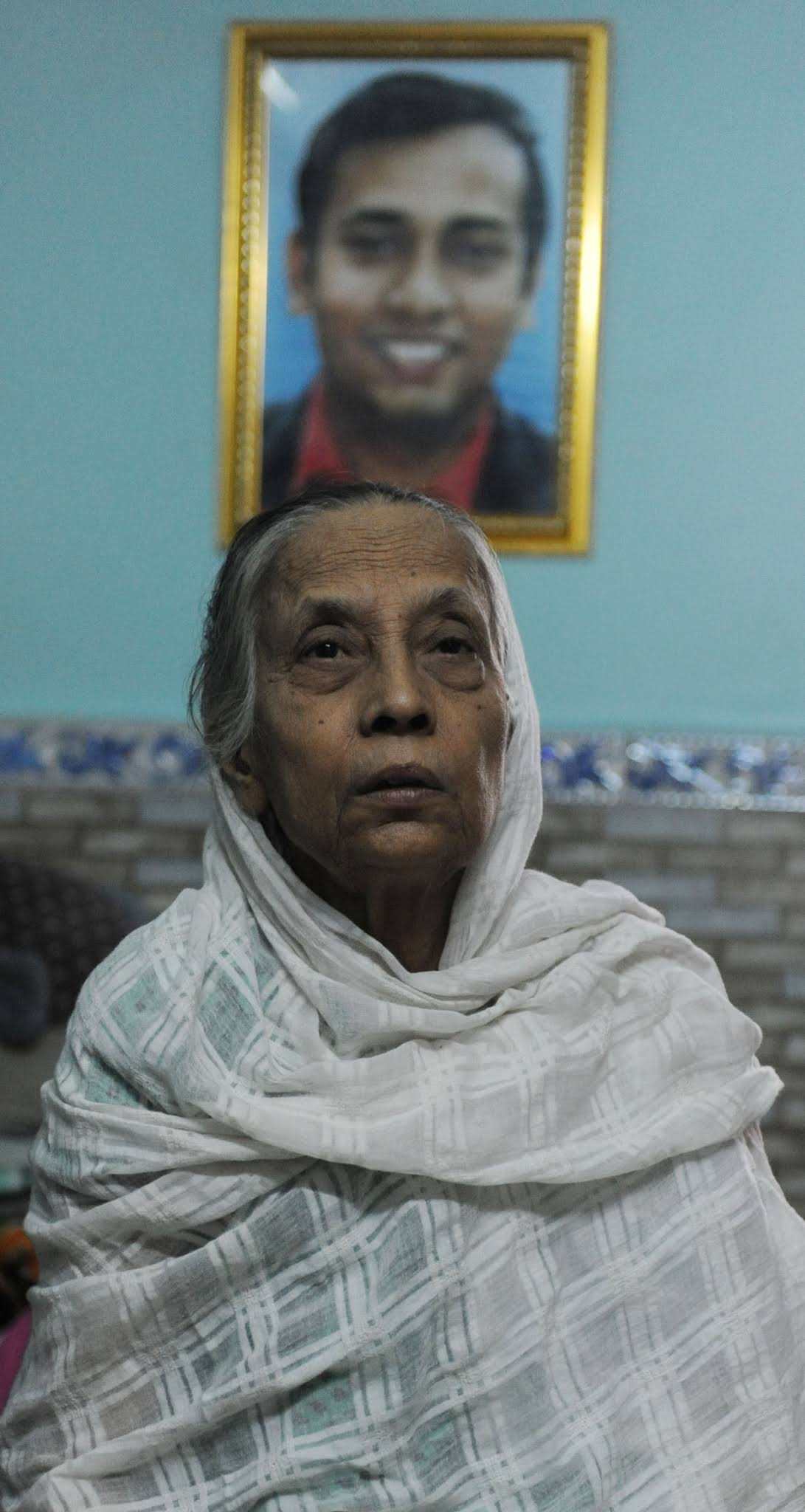 Rizwanur Rehman's mother sits in front of her dead son's portrait.