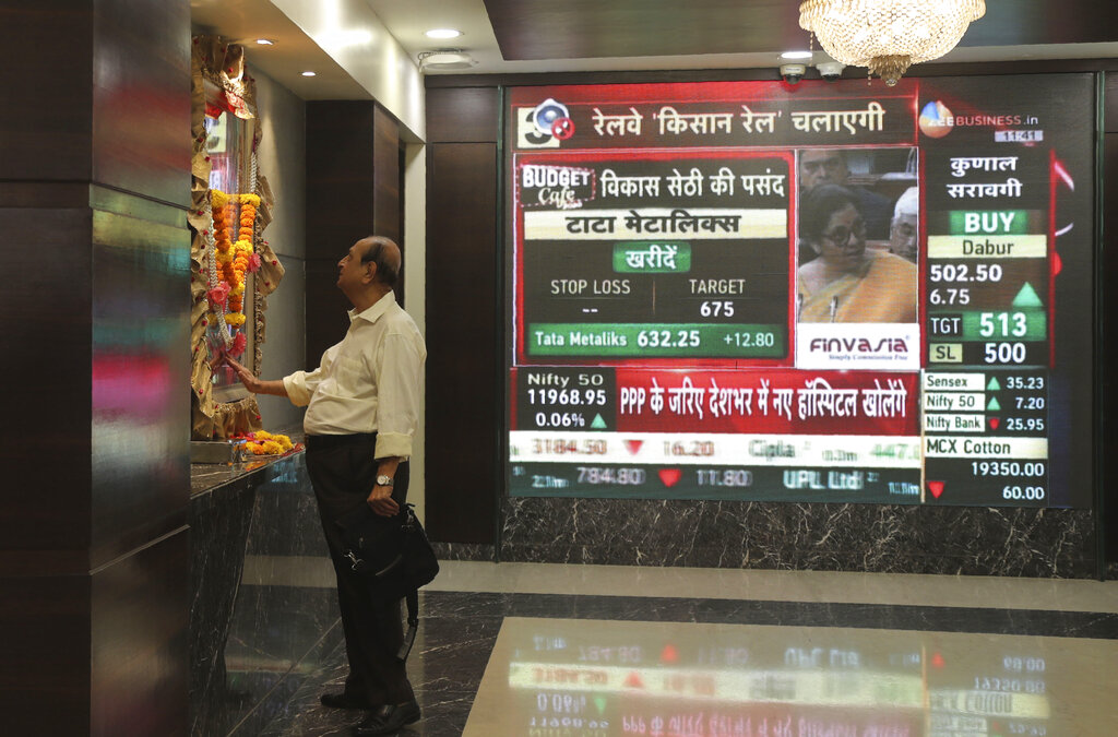 A man offers prayers to a Hindu goddess at the Bombay Stock Exchange (BSE) office, as Finance Minister Nirmala Sitharaman is seen on a television screen presenting the annual budget in Mumbai