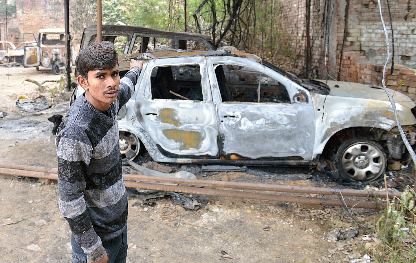 Bharat Ram, the farmhouse guard, points at some of the vehicles set on fire allegedly by policemen. He said they let him go when he revealed his identity