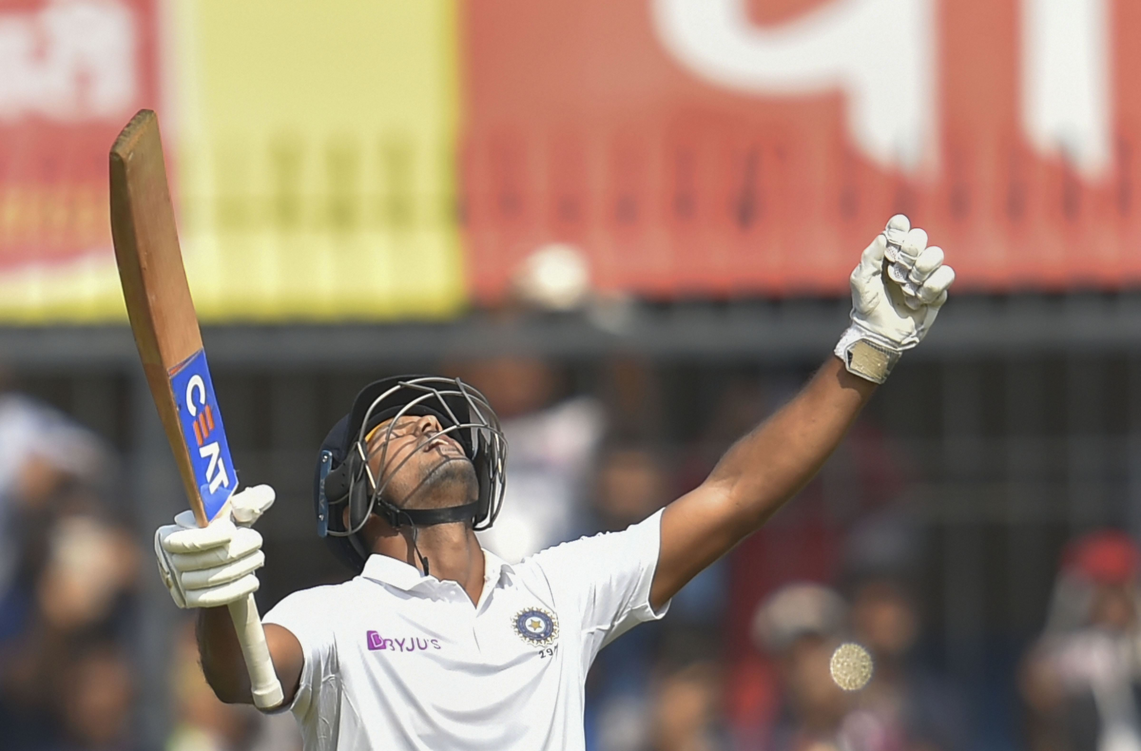 Indian batsman Mayank Agarwal holds up his bat as he reacts after scoring a century on the second day the first cricket test match against Bangladesh, in Indore, Friday, November 15, 2019.