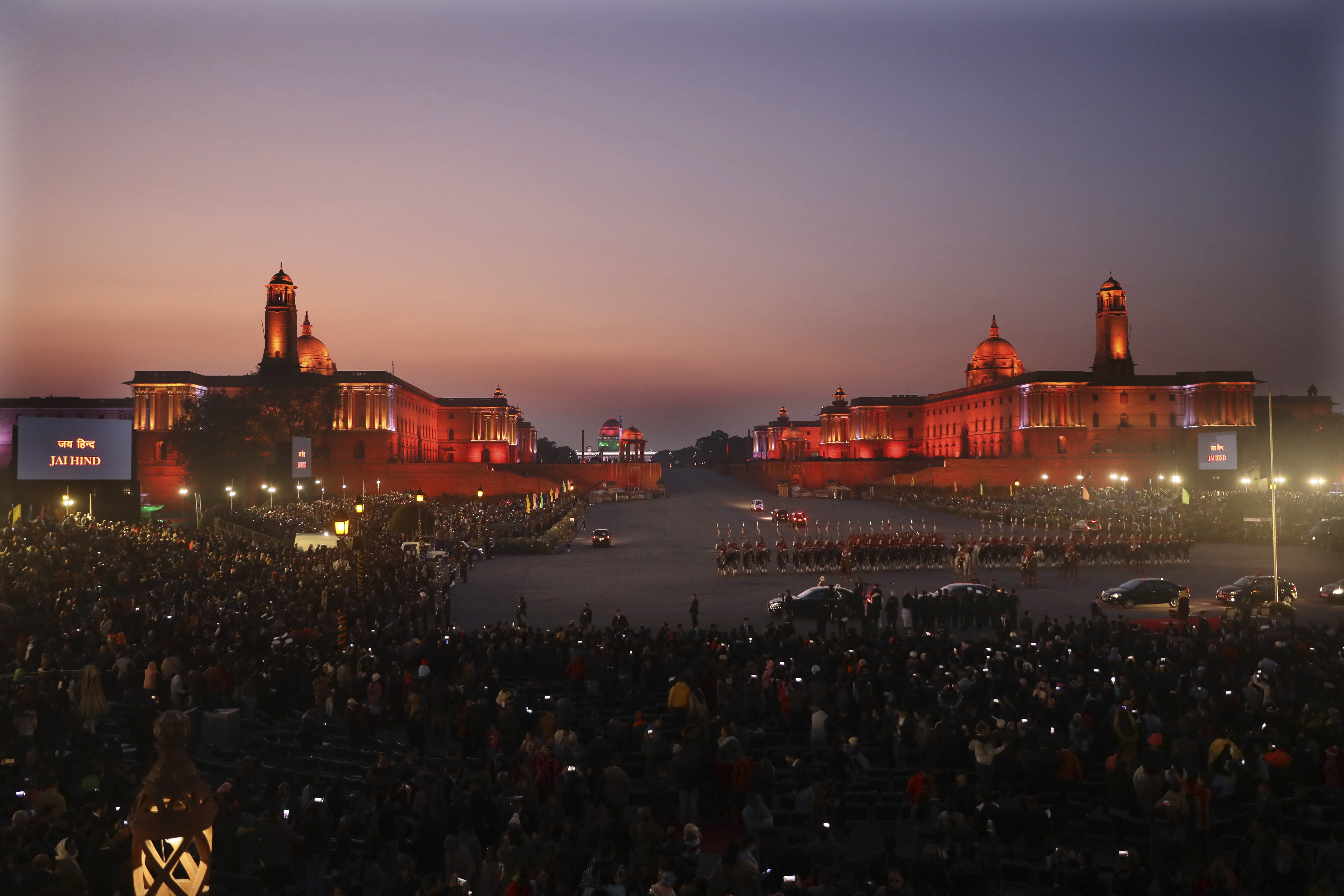 Members of the crowd hold up their mobile phones to take pictures of the illuminated Indian Presidential Palace, center, and the north and south blocks, the government seat of power, as the president leaves at the end of the Beating Retreat ceremony at Raisina hills, in New Delhi, India, Wednesday