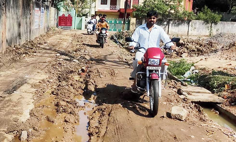 A motorcyclist tries to negotiate the muddy road in Kanke, Ranchi, on Saturday.
