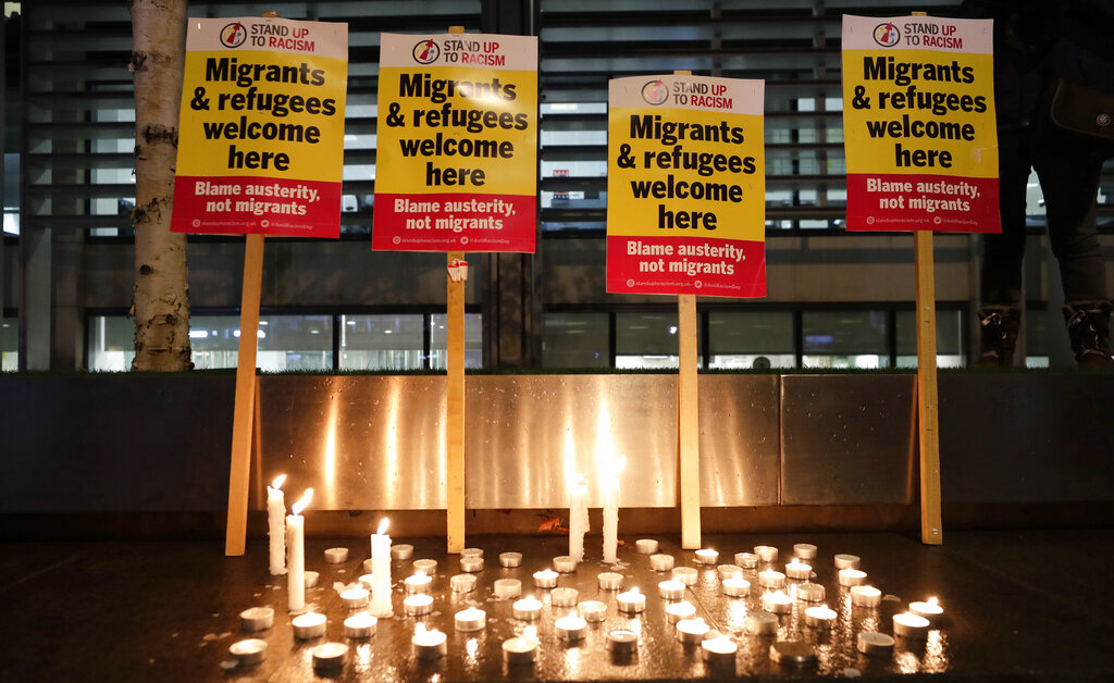 Signs and candles on a wall were placed at a vigil for the 39 truck victims, outside the Home Office in London, Thursday, October 24, 2019.