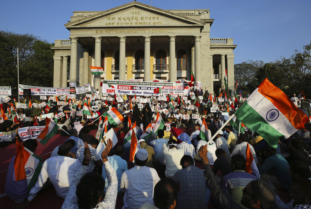 People holding national flags and placards, participate in a protest against a new citizenship law that opponents say threatens India's secular identity, in Bangalore