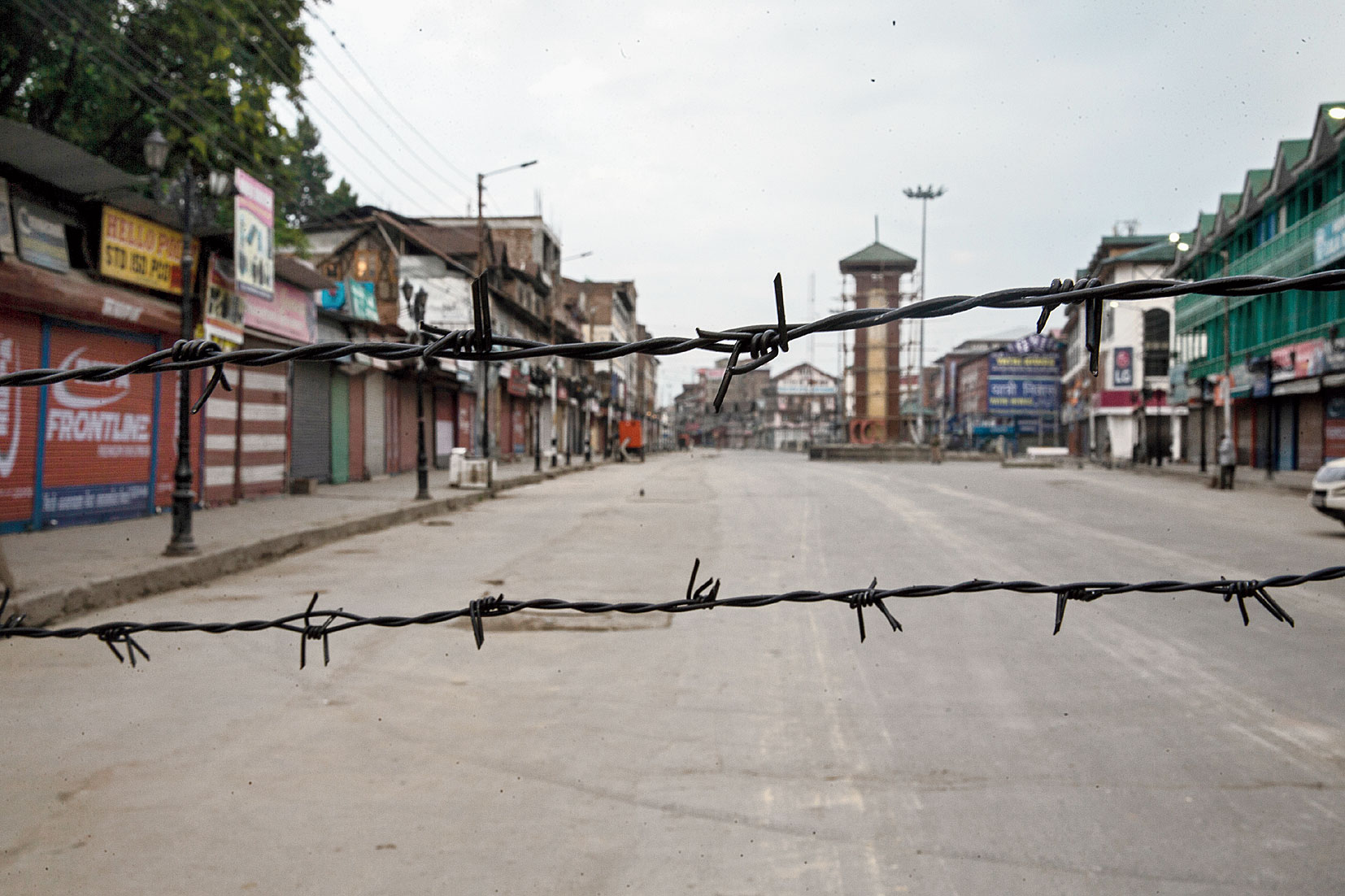 A deserted street is seen through barbwire that was strung as a blockade during curfew in Srinagar on August 6, 2019.