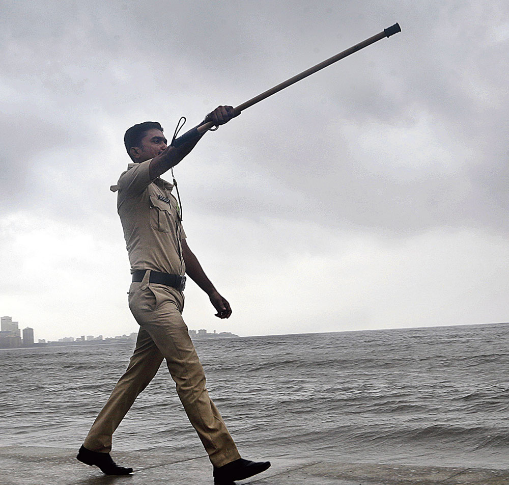 A policeman instructs people to keep a distance from the shoreline on the Arabian Sea coast in Mumbai on Wednesday