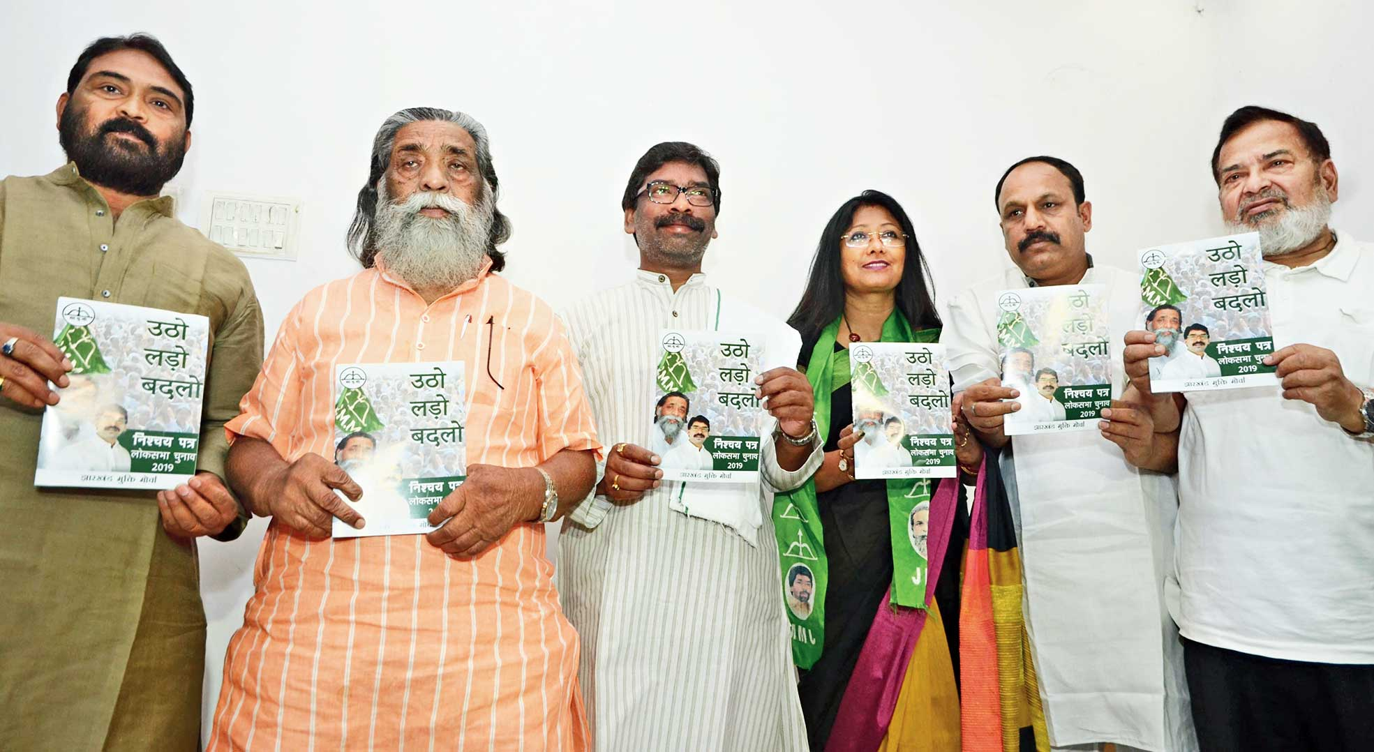 JMM chief Shibu Soren and son Hemant release the party's election manifesto at Morabadi in Ranchi.