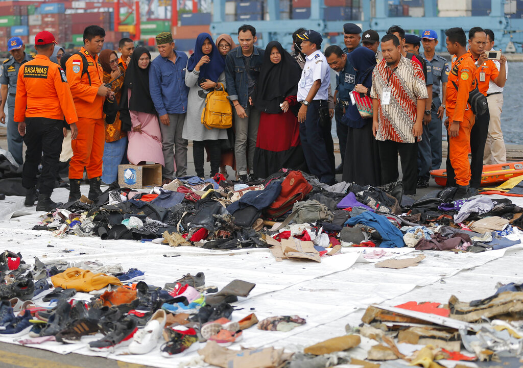 Relatives of passengers of a crashed Lion Air jet check personal belongings retrieved from the waters where the airplane is believed to have crashed, at Tanjung Priok Port in Jakarta,  on October 31, 2018.