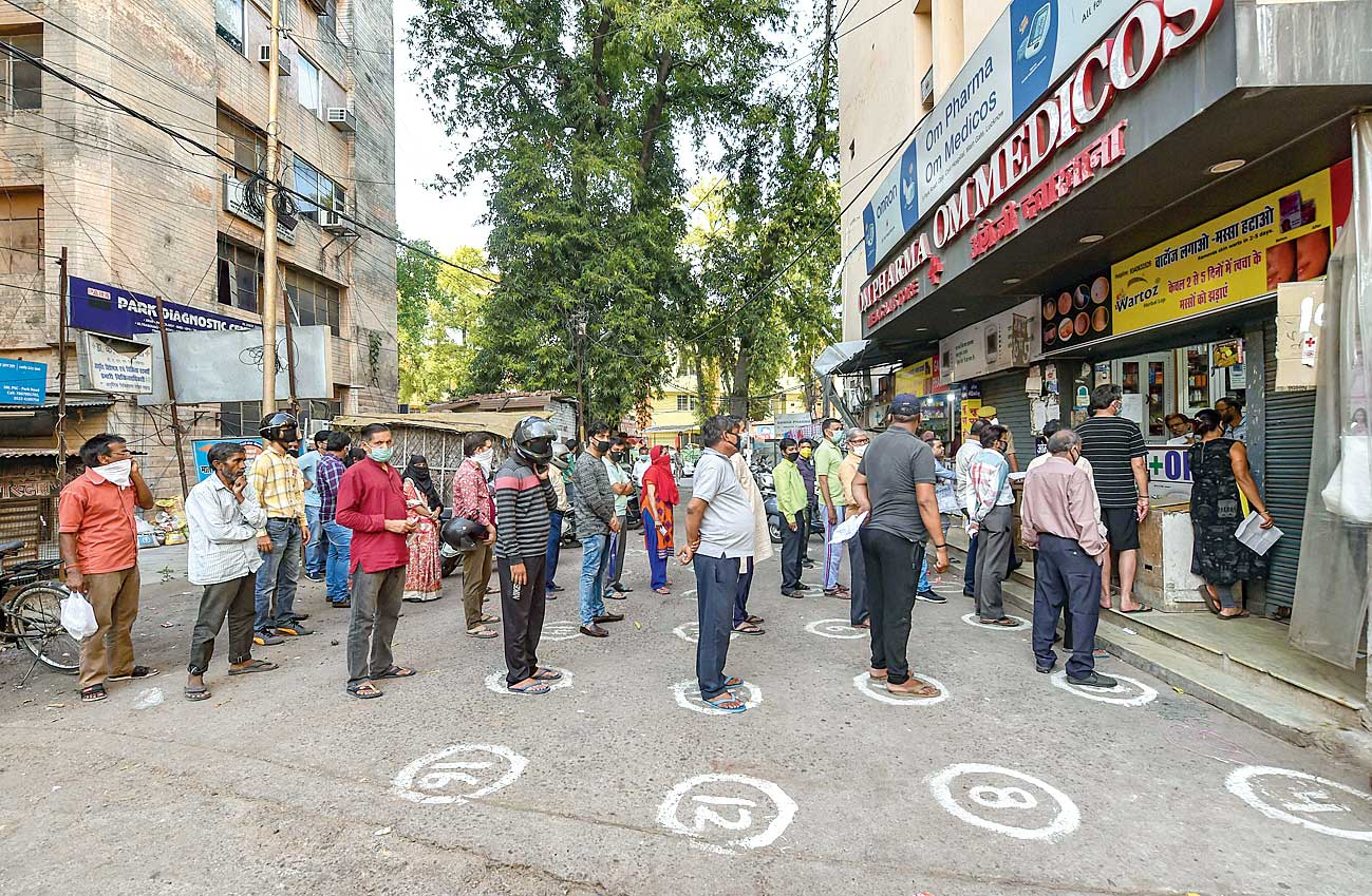People observe social distance while waiting outside a chemist's shop in Lucknow on Wednesday.