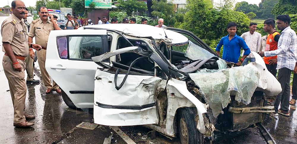 Police stand near the wreckage of the car in which the Unnao rape survivor was travelling during its collision with a truck near Raebareli, Sunday, July 28, 2019.