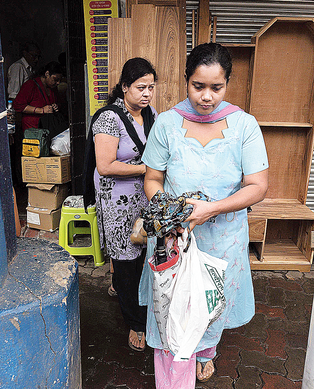 Residents of Durga Pituri Lane leave their home with some of their belongings on Sunday.