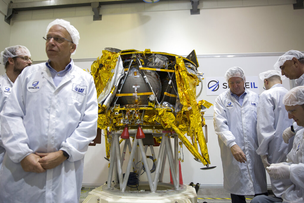 Technicians stand next to the SpaceIL lunar module, on display in a special clean room during a press tour of their facility near Tel Aviv, Israel, on December 17, 2018.