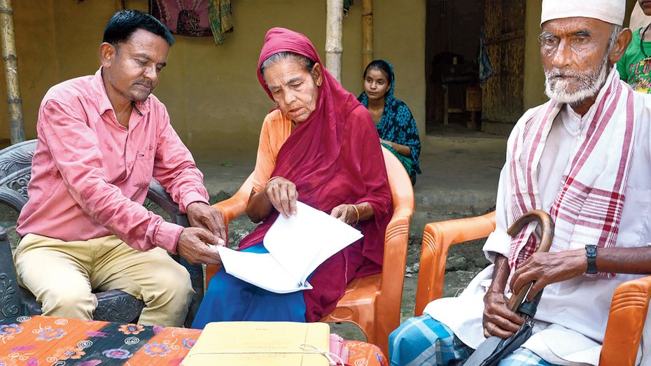 Family members check their names in the NRC final list in Gorbhetar village in Baska district