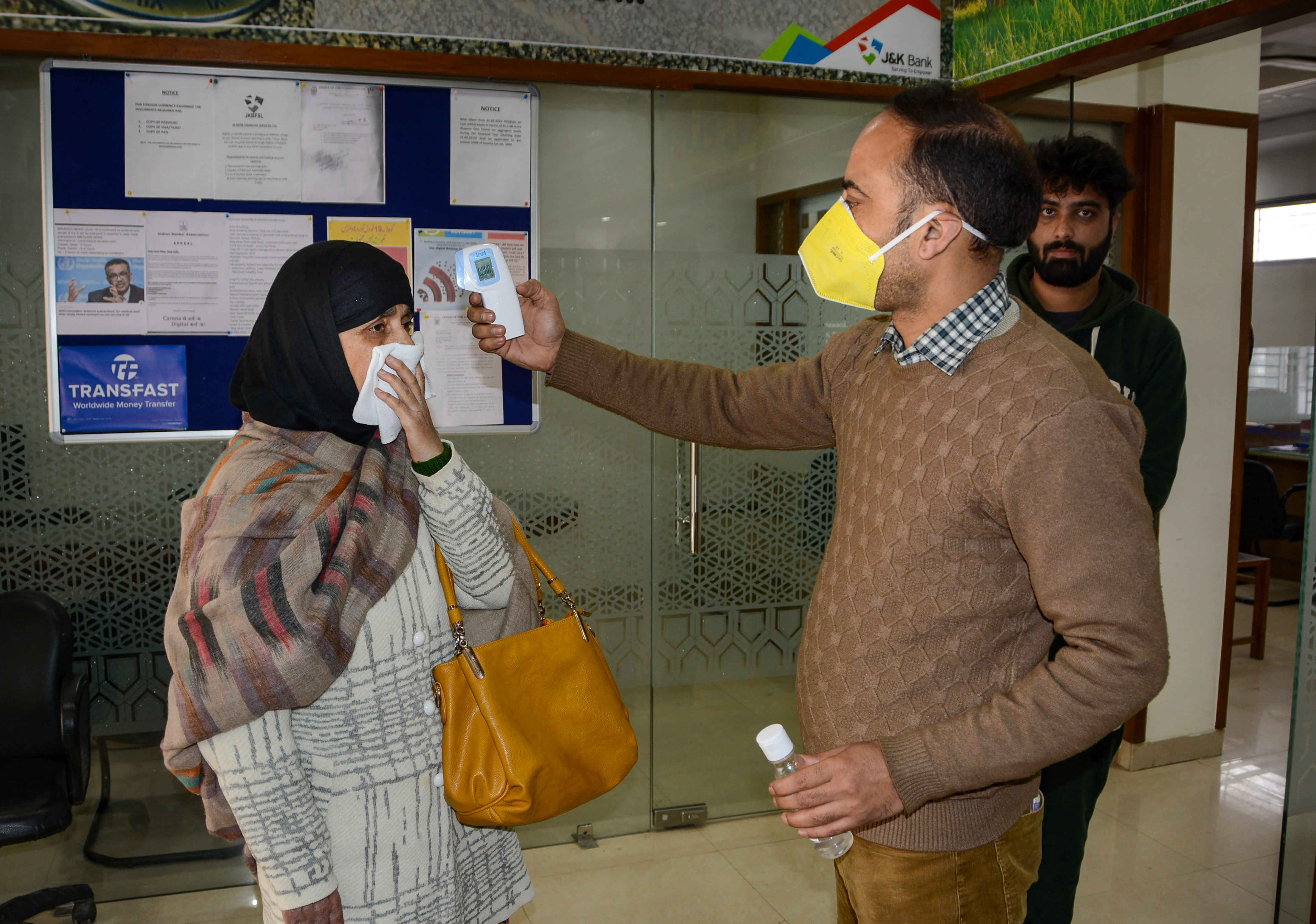 An official measures the temperature of a visitor using an infrared thermometer at the entrance of a bank, following the outbreak of coronavirus, in Srinagar, Monday March 23, 2020