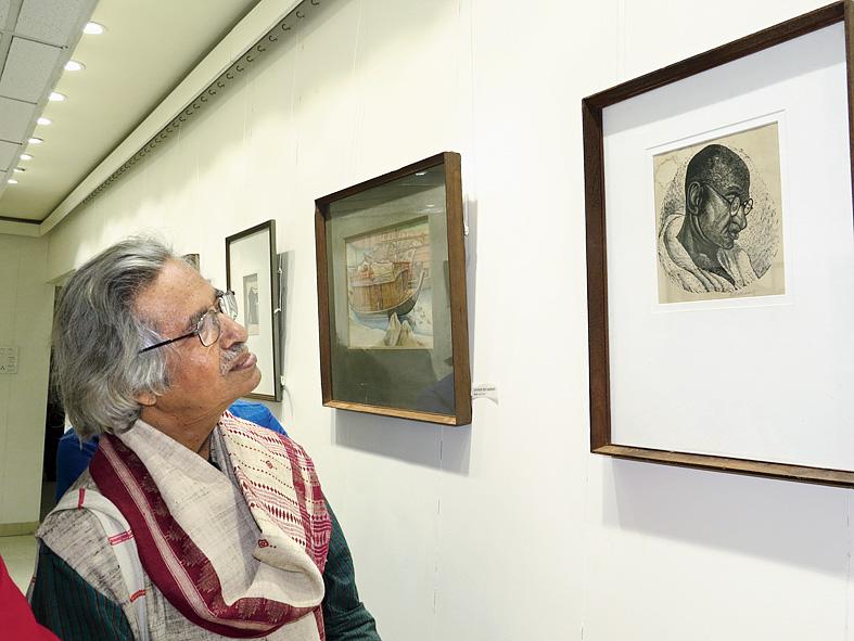 Jogen Chowdhury admires a woodcut Gandhi by Ramendranath Chakraborty.