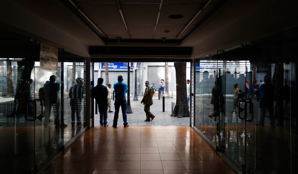 People walk past darken store fronts in Caracas, Venezuela on Friday, March 8, 2019.