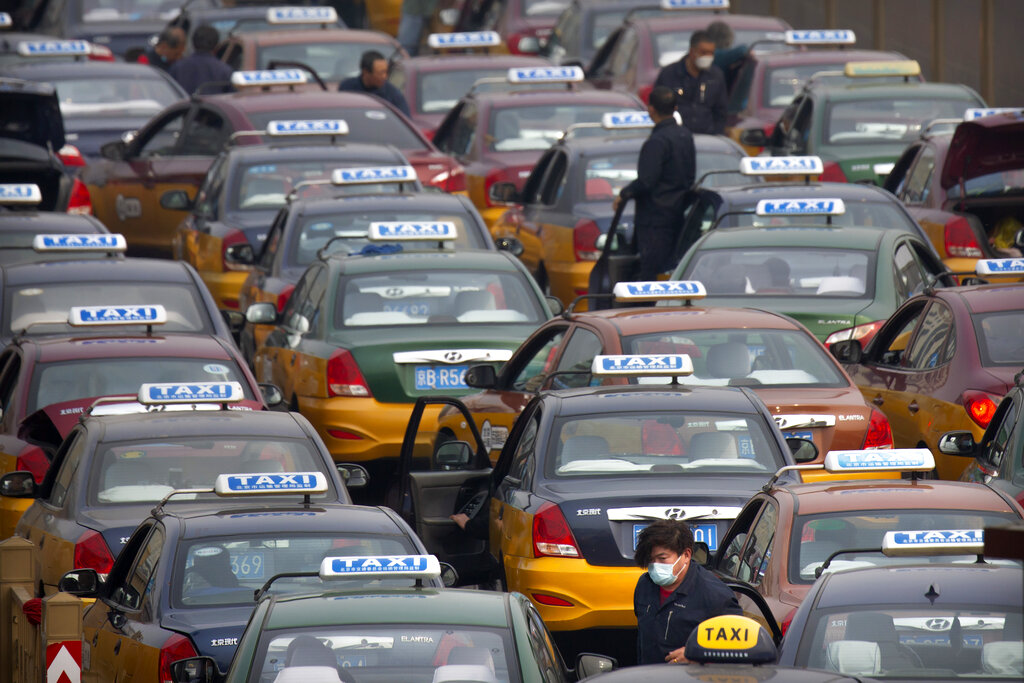 A taxi driver wearing a face mask stands in the taxi queue at the Beijing Railway Station in Beijing, Wednesday, March 25, 2020.