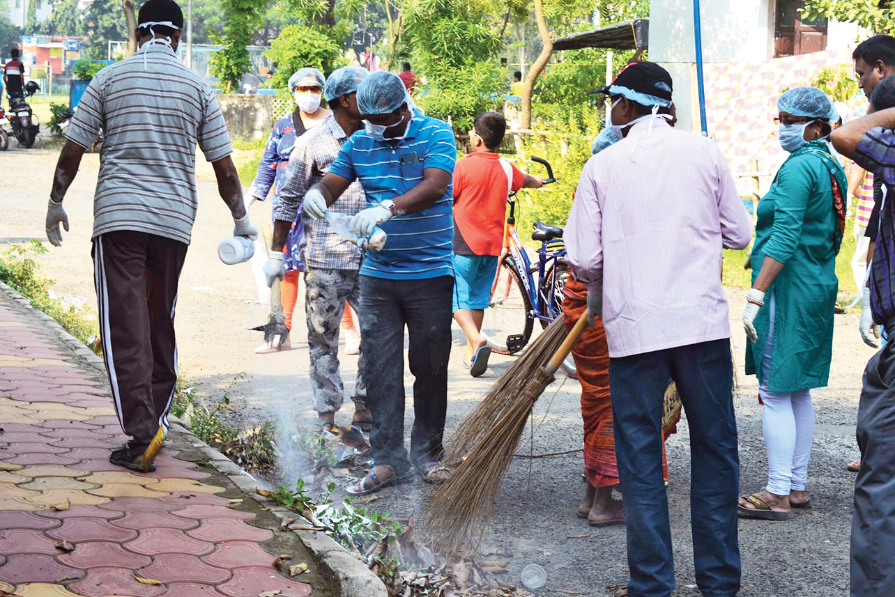 Residents wield the broom and spray bleaching powder on Sunday.
