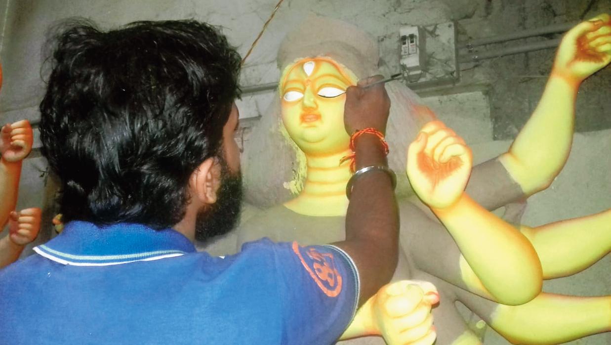 An artistan works on an idol in Karimganj.