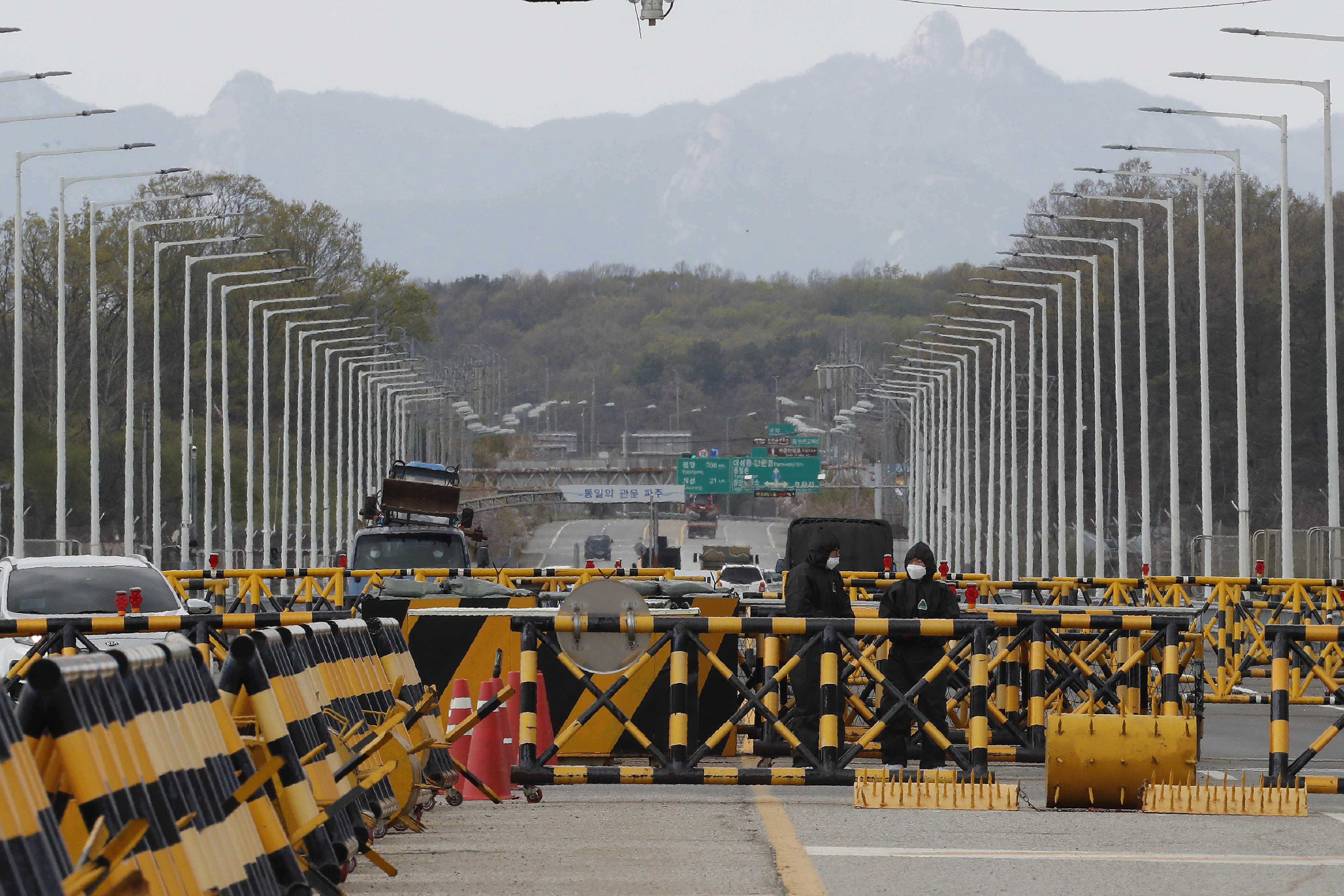 South Korean army soldiers wearing protective suits stand guard at the Unification Bridge, which leads to the Panmunjom in the Demilitarized Zone in Paju, South Korea