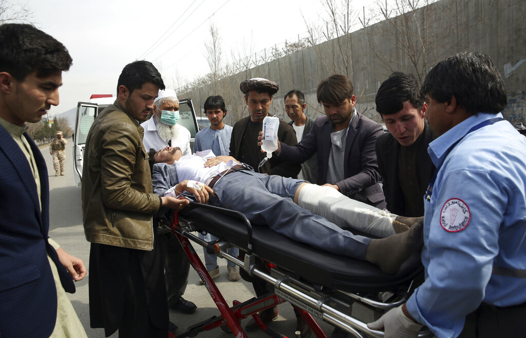 An injured man is carried into an ambulance after an attack in Kabul on Friday