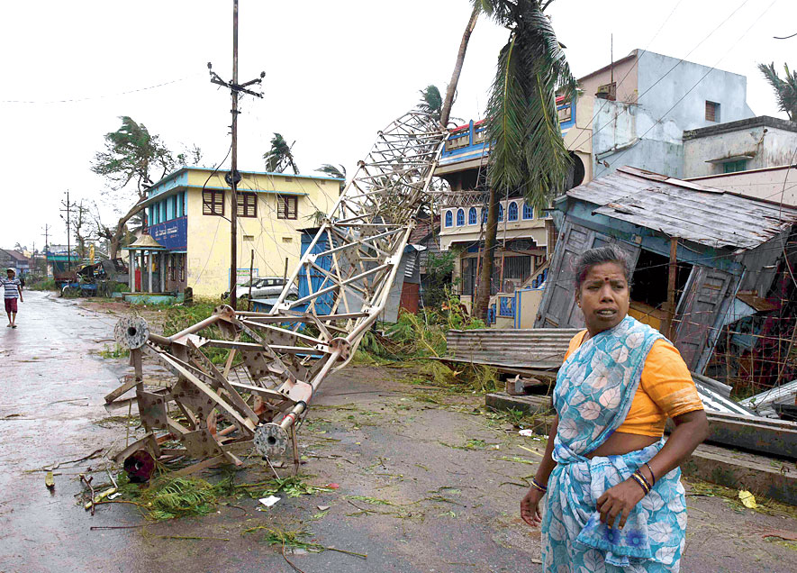 A woman stands next to a damaged communication tower after cyclone Titli hit in Srikakulam district
