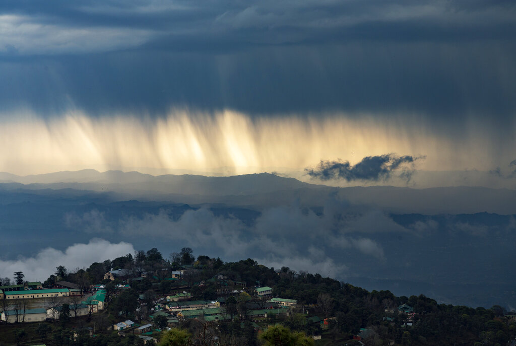 Streaks of rain and dark clouds are seen over the Kangra Valley in Dharmsala, on Saturday