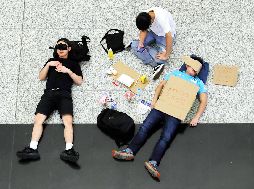 Protesters sleep during a protest at the Hong Kong International Airport, Monday, August 12, 2019.