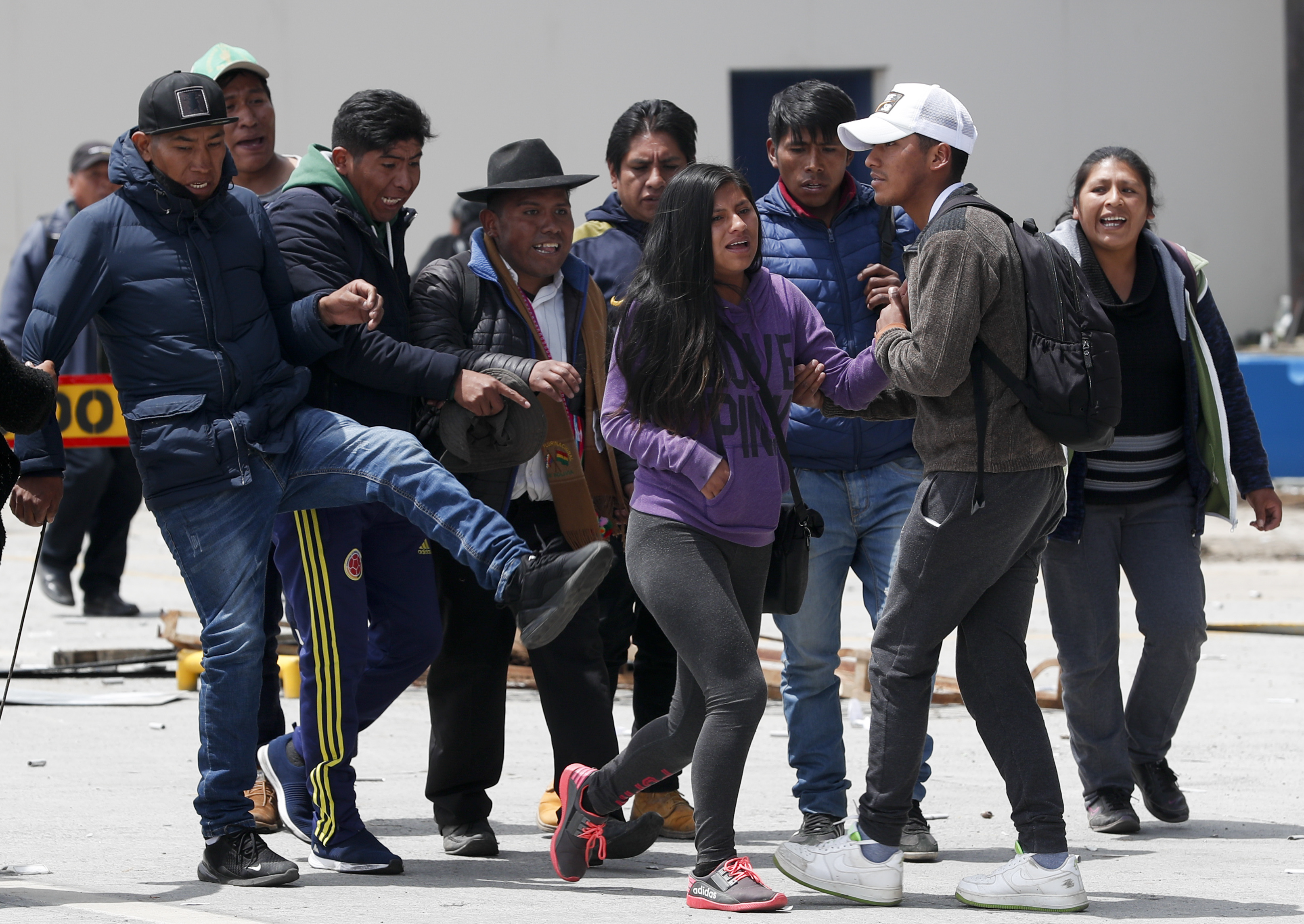 One person that is part of a group of followers of President Evo Morales kicks towards a couple in La Paz, Bolivia, Sunday, November 10, 2019